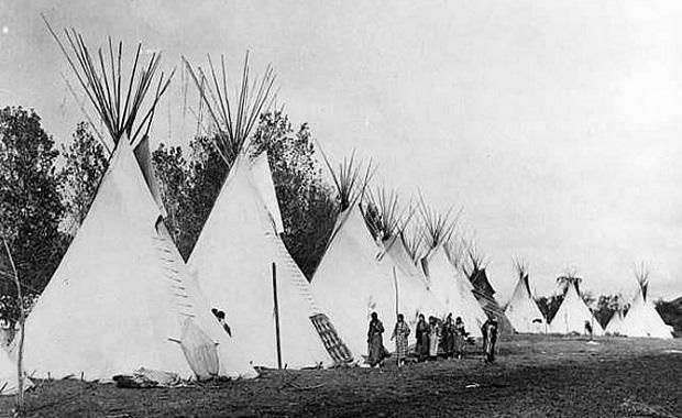 Les femmes indiennes se tiennent devant leur camp de tipis. Cette image des Indiens Crow dans le Montana a été prise autour de 1890. Certains groupes indiens ont continué à vivre dans des tipis jusqu'au début des années 1900.
