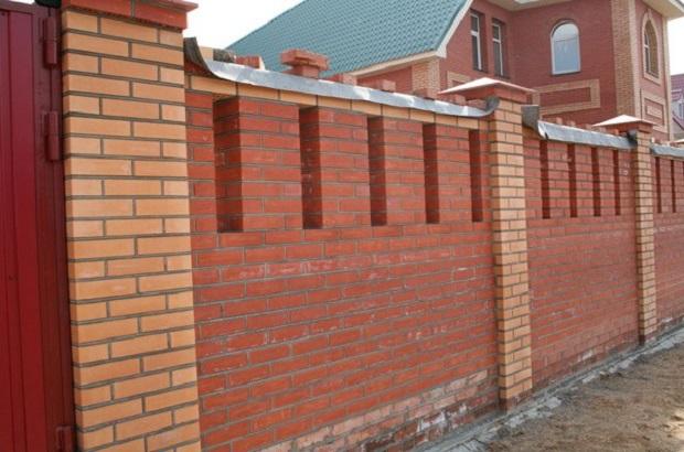 Dacha typique d'une personne riche dans les années 90 : une maison de brique rouge qui est cachée derrière une haute clôture en briques rouges